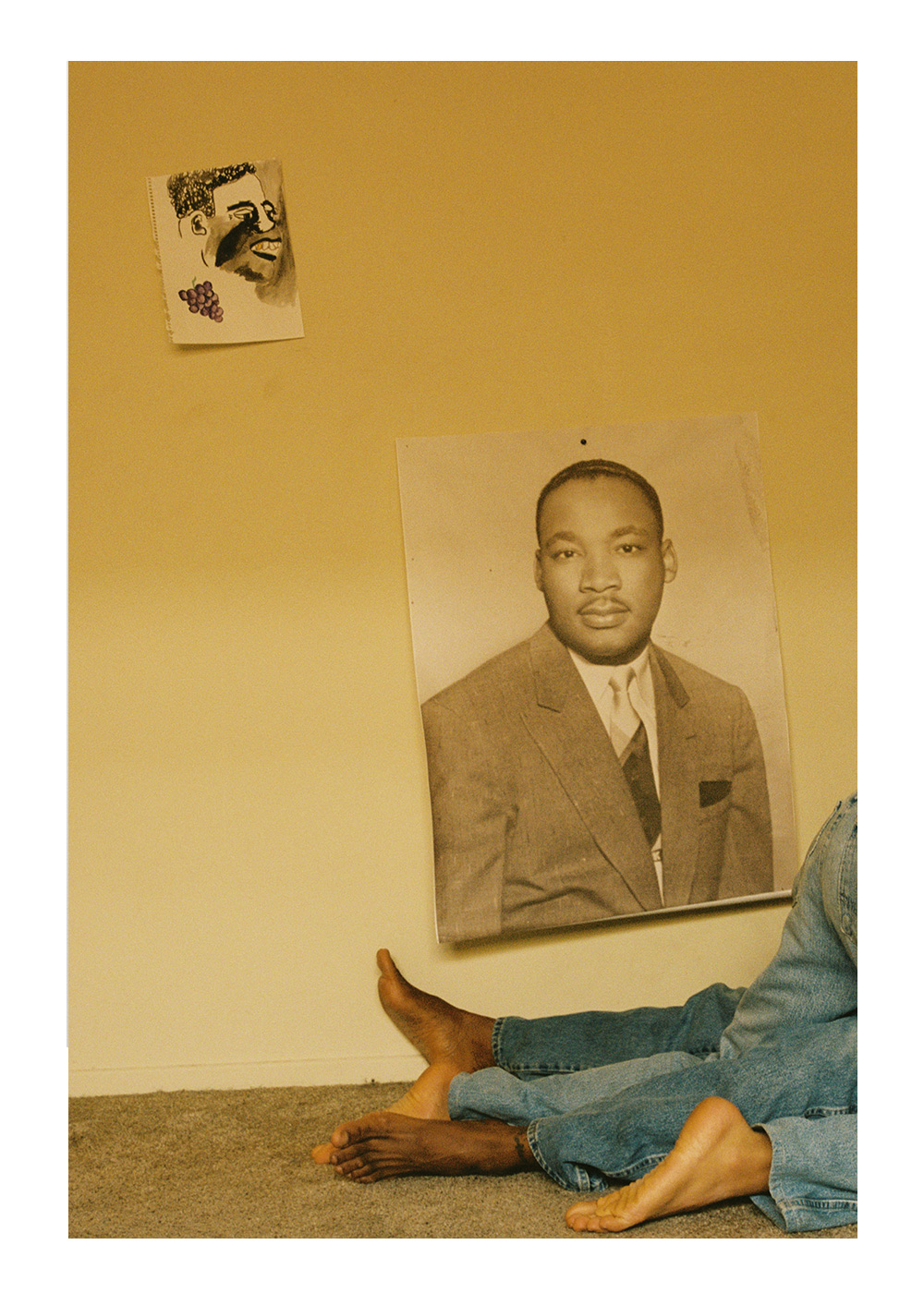 A photograph in a room with a yellow wall and a taupe-colored carpeted floor. There are two prints on the wall. One print is of Martin Luther King Jr. wearing a suit and tie. The other is an abstract rendering of a figure's face with a bunch of grapes in the lower left-hand corner. In the bottom right of the photograph, there are two intertwined pairs of legs clad in jeans and barefoot. One of the figures appears to be on their knees, while the other figure appears to be on their back.