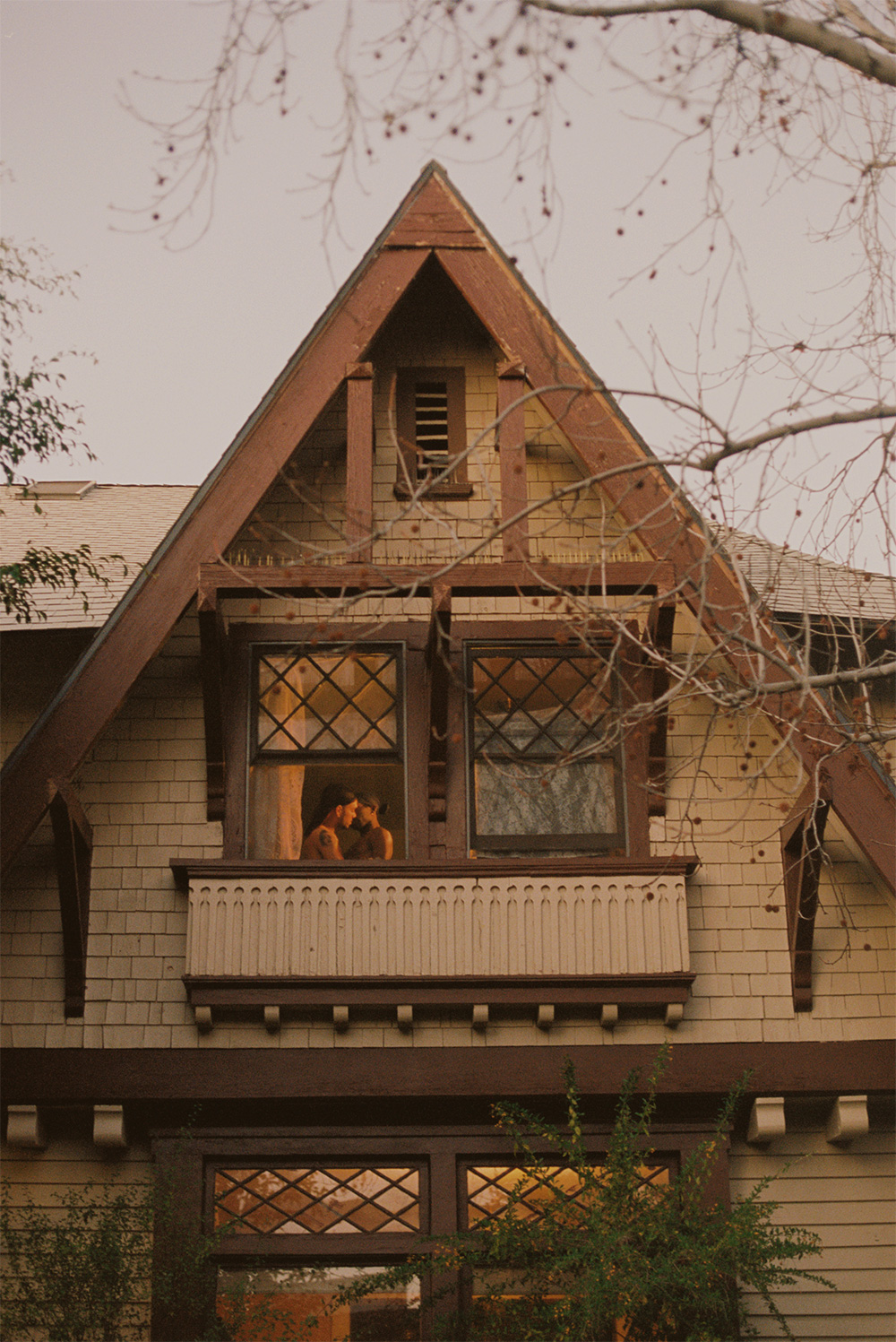A photograph featuring the top half of a beige and brown paneled house, which centers two windows on the top floor. One of the windows is open, and has a sand-colored curtain drawn aside, beyond which two figures are visible from the chest up. The figures have their naked torsos angled towards one another and their faces touching. The other window is covered by a gray material.