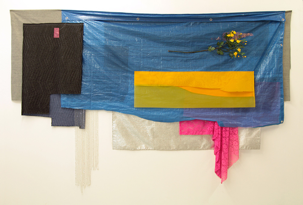 A large assemblage of different fabrics and materials layered over one another, mainly in shades of grey and blue, forming an irregular shape longer than it is tall. At the center is a large rectangular blue tarp simulating a body of water, folded over with rivets on top. On top of it is a long-stemmed branch of yellow flowers and a golden yellow piece of fabric. A piece of hot pink lace hangs from the bottom right of the tarp.