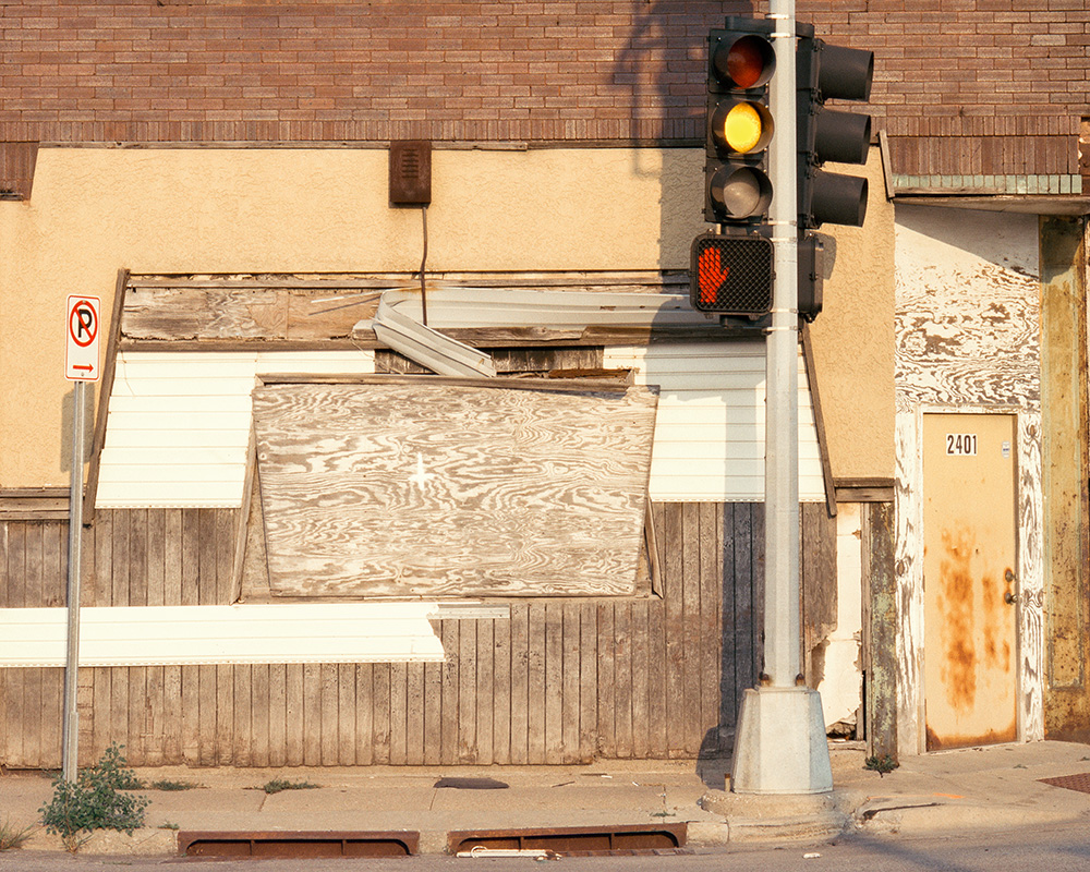 A photograph of a street corner featuring a building boarded-up with wood in shades of brown and white. The brick of the building is visible at the top of the photograph. At the bottom right of the photograph, there is a rusty beige door numbered 2401. Off-center to the right, in front of the building there is a stop light. The traffic light is yellow, and the pedestrian signal shows a red hand.