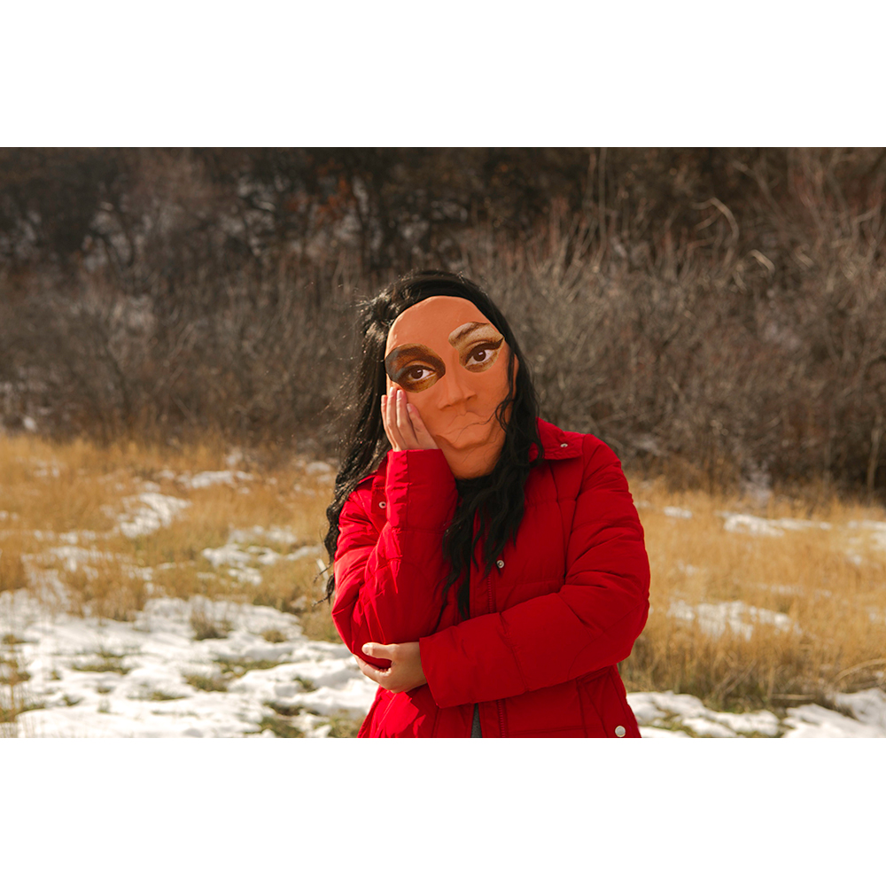 A photograph of a person with long black hair wearing red puffer coat and a mask with cut and pasted eyes. The person has their right hand on their left elbow, and their left hand on their left cheek. They are standing in a field of yellow shrubs and snow. In the background, there are bare branches of trees.