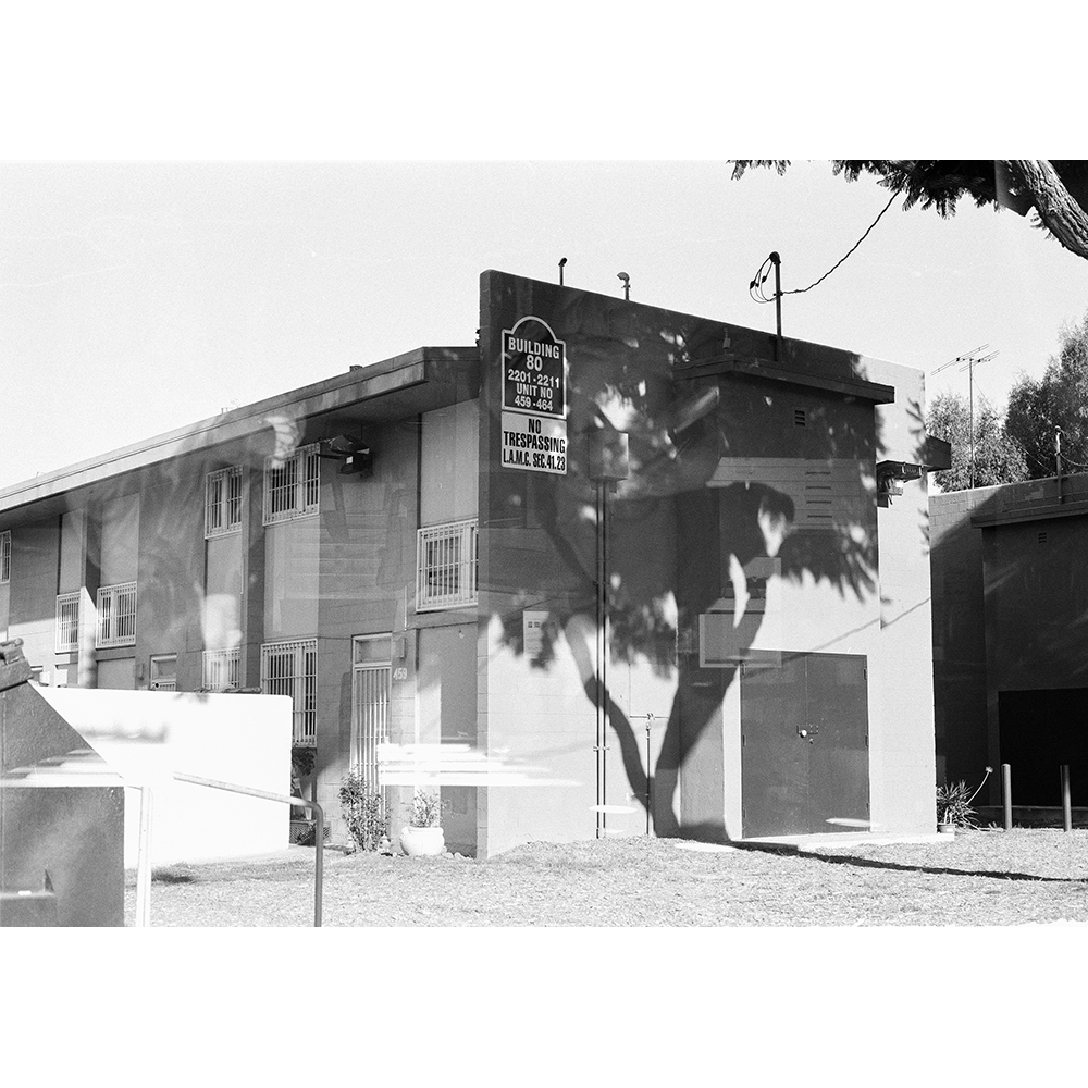"""A black-and-white photo of a two story residential building, short and close to the grassy ground. There are bars on the doors and windows. There is a sign on the side of the building that says """"Building 80 2201 2211"""" and, below it, another sign that says """"No Trespassing"""""""