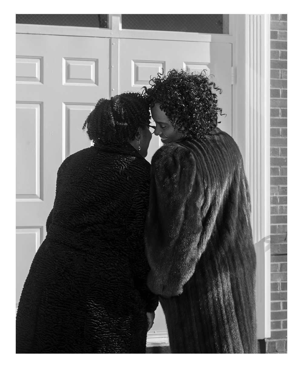 Two Black femmes with shortish curly hair wearing fur coats, pressing up against each other and smiling. We are viewing them from the back, but we can see one femme turning to say something in the other's dangly-earring'ed ear, smiling. In the background is a large wooden door they are standing in front of.