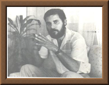 Black and white image of Puerto Rican poet Salvador Villanueva as a young man. He has coarse black hair and beard. He wears a white button-down shirt with rolled up sleeves at the elbows. It seems he is gesturing to someone off-screen in the middle of conversation.
